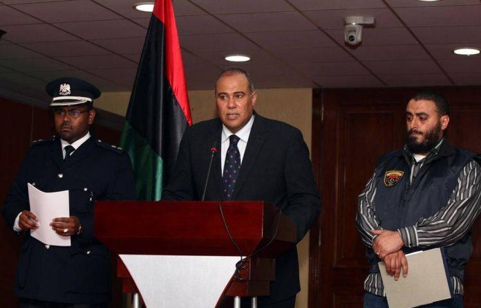 Libyan government spokesperson Nasser al-Manaa speaks as Salem Ahbaj