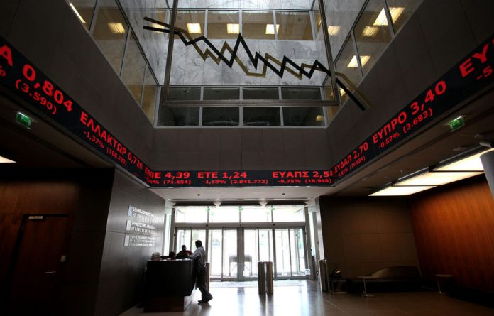 Employees chat under screens showing falling stocks at the Athens Stock Exchange.