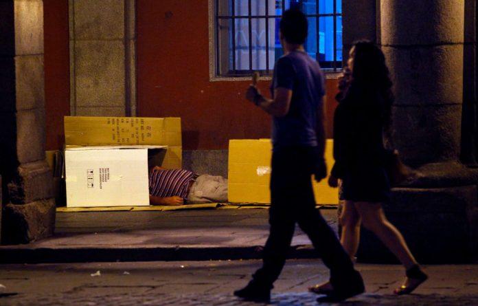 A couple walks past a man sleeping in a cardboard box in Madrid