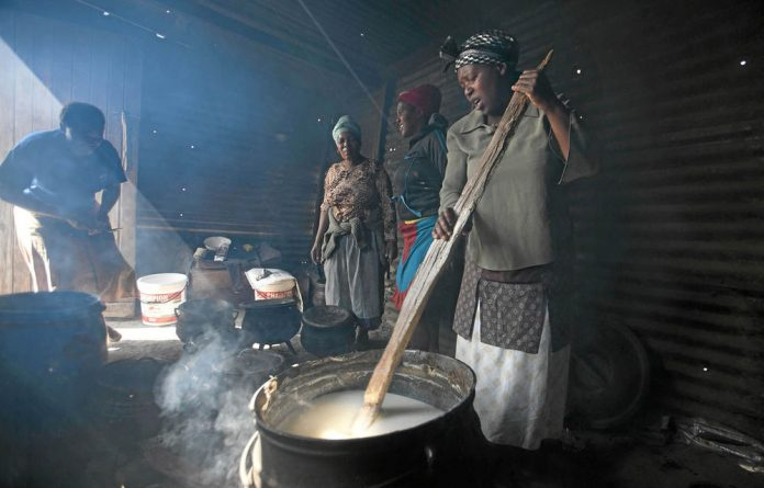 Community women assist the family prepare food for the Saturday funeral of Semi Jokanisi