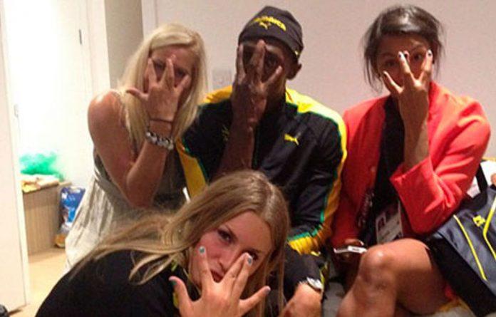 Usain Bolt celebrates his 100m gold medal with three members of the Swedish women's handball team.