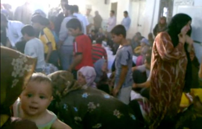 This image made from amateur video purports to show families gathered around bodies of victims in Tremseh.