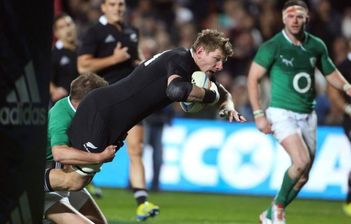 New Zealand's Adam Thomson dives over to score a try against Ireland during the international third test rugby match at Waikato Stadium in Hamilton