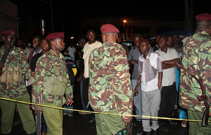Kenyan police officers secure the scene of a grenade attack
