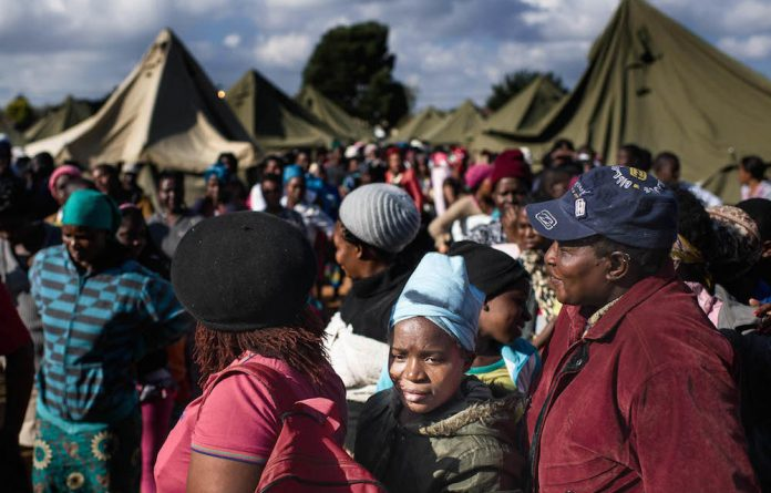 People displaced by xenophobic attacks wait in a temporary camp