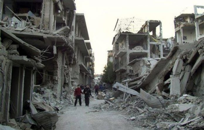 Syrian citizens walk in a destroyed street that was attacked on Wednesday by Syrian warplanes.