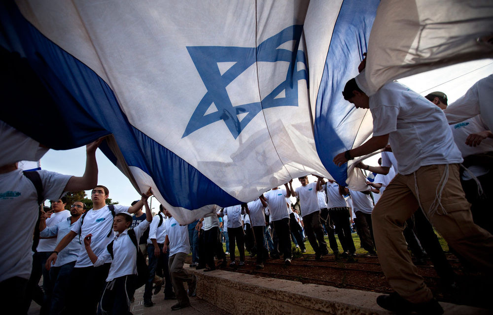 Israeli youths wave Israeli flags during a march celebrating Jerusalem Day in front Damascus Gate in Jerusalem's Old City.