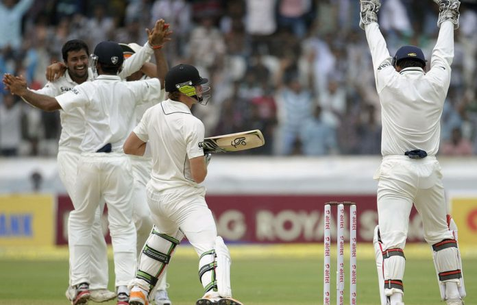 Indian cricketer Pragyan Ojha celebrates the dismissal of New Zealand cricketer Martin Guptill during the third day of the first Test match between India and New Zealand.