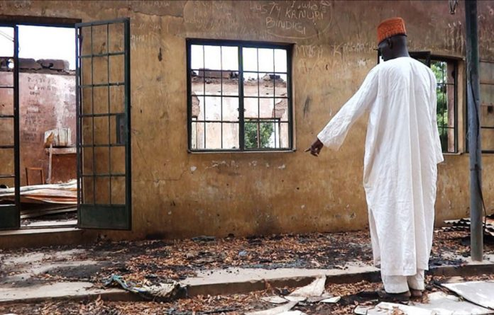 A teacher inspects a burnt school hostel at the Government Secondary School of Mamudo in north-east Nigeria where Boko Haram gunmen launched attacks.