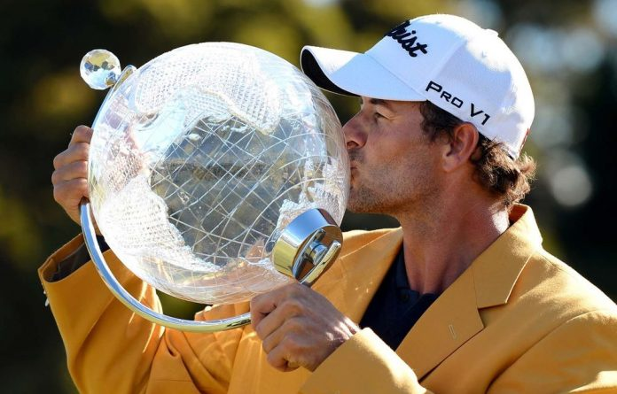 Adam Scott of Australia kisses the trophy after winning the Australian Master golf tournament at the Kingston Heath golf course in Melbourne.