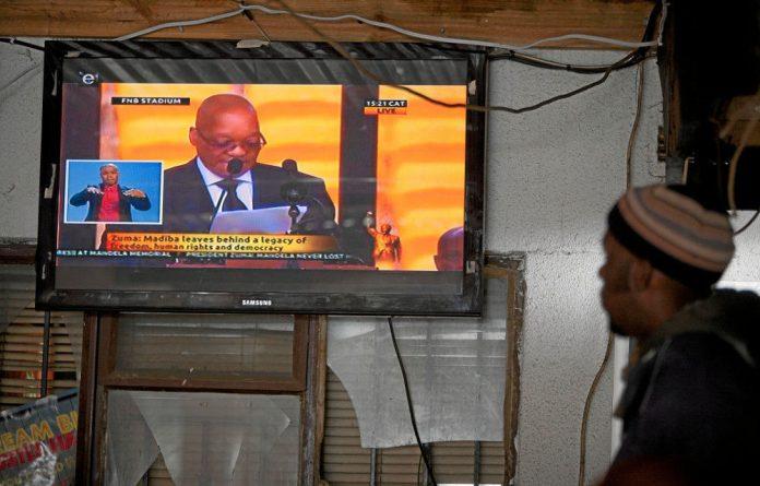 A man watches President Jacob Zuma's speech at Nelson Mandela's memorial service