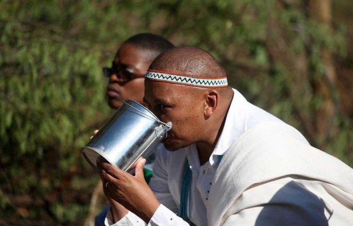 Phathekile Holomisa drinks umqombothi after a traditional cleansing ceremony.