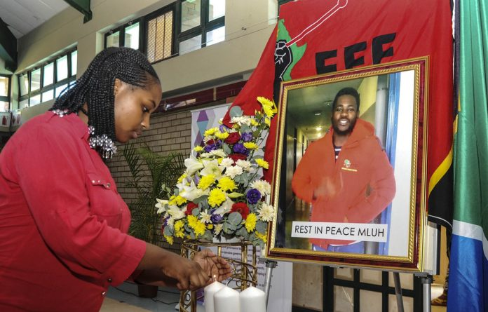 Zinhle Majozi lights candles next to a portrait of Mlungisi Madonsela during a memorial service. He was shot outside the Durban University of Technology during clashes between students and security guards. Photo: Jabulani Langa/Gallo Images/Daily Sun