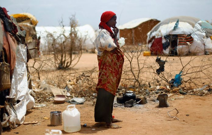 A refugee poses outside her hut in Dagahaley refugee camp north of Dadaab