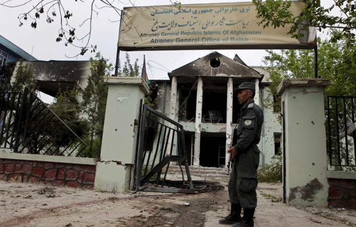 An Afghan police officer guards the Mazar-i-Sharif court the Taliban attacked on April 10