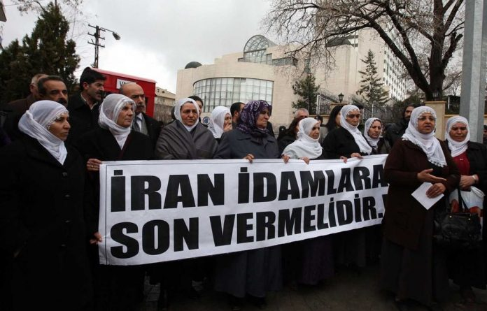Kurdish women carry a banner that reads 'Iran should end executions' as they protest against the Iranian regime outside the Iran embassy in Ankara