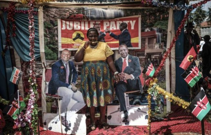 A woman eats an ice-cream while posing for a photograph between posters of Kenya's President Uhuru Kenyatta and Vice-President William Ruto at a temporary photo studio next to Kasarani Stadium during the president's inauguration ceremony