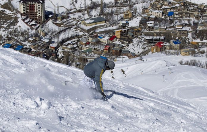 From sea to snow: Snowboarding at Iran's Shemshak ski resort and calm waters off Kish Island.