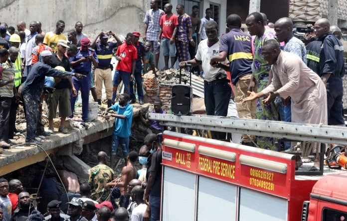 People watch rescue workers at the site of a collapsed building containing a school in Nigeria's commercial capital of Lagos