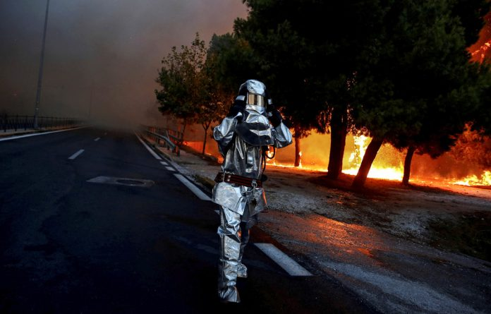 A firefighter wears a flame resistant uniform as wildfire burns in the town of Rafina