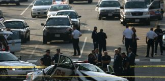 Law enforcement personnel gather around a police vehicle that was involved in the car chase in Washington DC.