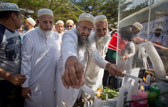 Kenyan's lay flowers and light candles at a memorial event organized by the Muslim community to pay their respects to those who died and those who helped others escape.