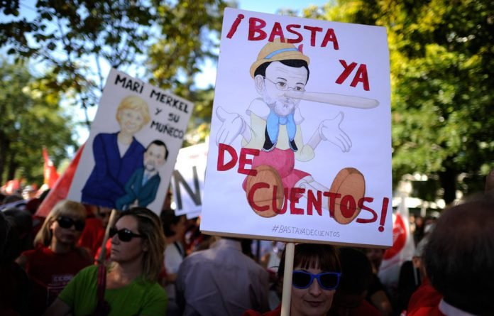 A protester holds a banner depecting Prime Miniuster Mariano Rajoy dressed as pinocchio reading
