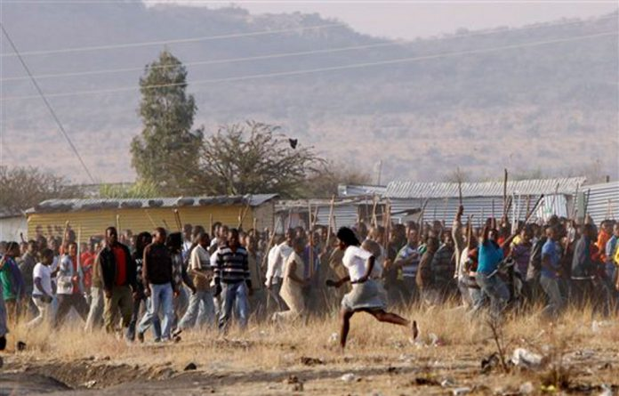 A woman runs in front of striking mineworkers during tense moments at the Lonmin mine near Rustenburg