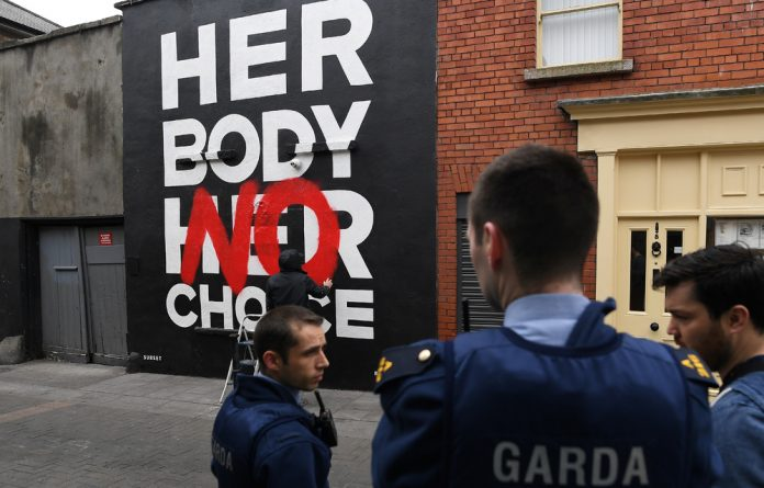 Police are seen at a new Pro-Choice mural by a graffiti artist collective called 'Subset' ahead of a 25th May referendum on abortion law