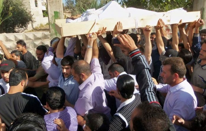 Anti-Syrian regime mourners carry the body of soldier Khaled Shurbajy in Damascus on Saturday