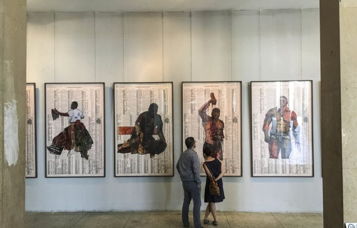 Body of work: Visitors check out paintings by Godried Donkor in the Ancien Palais du Justice. Njami convinced the Senegalese authorities that the majestic abandoned building was the perfect venue for the Dak'art biennale