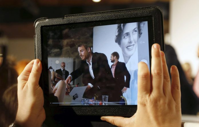A journalist takes a picture with a tablet device