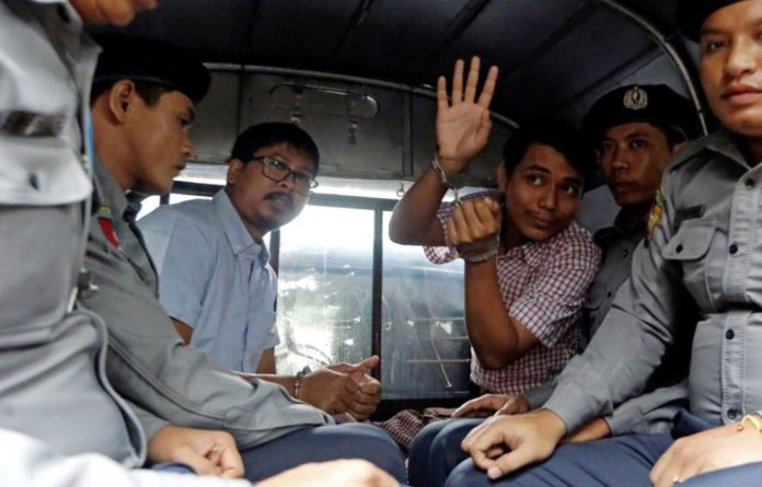 Detained journalists Wa Lone and Kyaw Soe Oo sit beside police officers as they court in Yangon