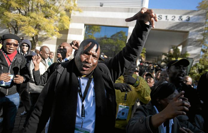 Anti-Jacob Zuma delegates at the ANC policy conference in Midrand make the sign of a shower head to express their disapproval of the party president.