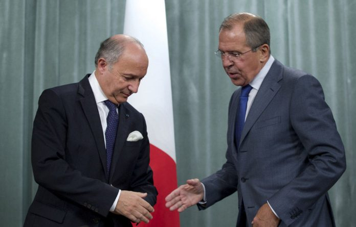 French Foreign Minister Laurent Fabius and his Russian counterpart Sergey Lavrov shake hands at the end of a news conference after their meeting in Moscow on Tuesday.