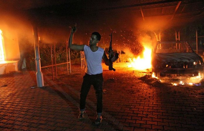 A man waves his rifle as cars and buildings burn in the US consulate compound in Benghazi.