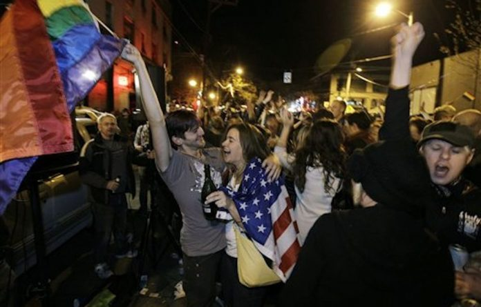Revelers display US and gay pride flags as they celebrate the legalisation of gay marriage in Washington state.