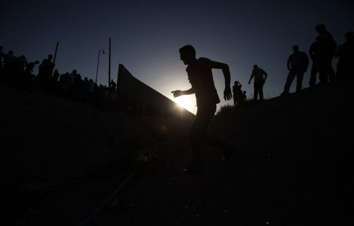 Palestinian men clash with Israeli police at the Qalandia checkpoint
