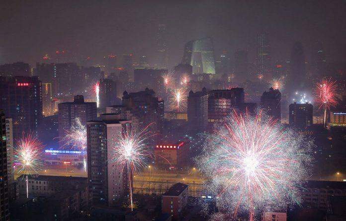 Fireworks illuminate the smoggy Beijing skyline as China brings in the new year.