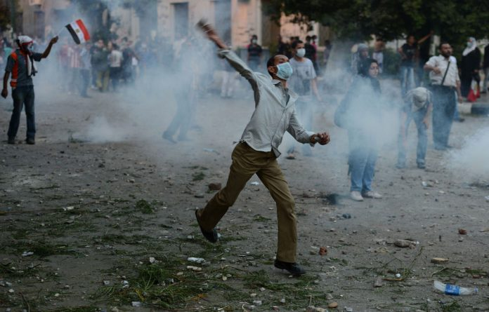 Egyptian protesters throw stones towards riot police during clashes near the US embassy in Cairo.