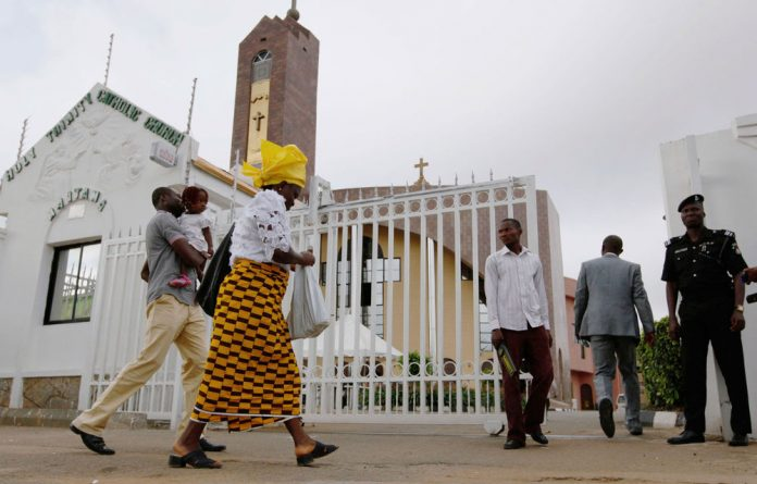 Worshippers arrive at Holy Trinity Catholic Church in Abuja on June 24