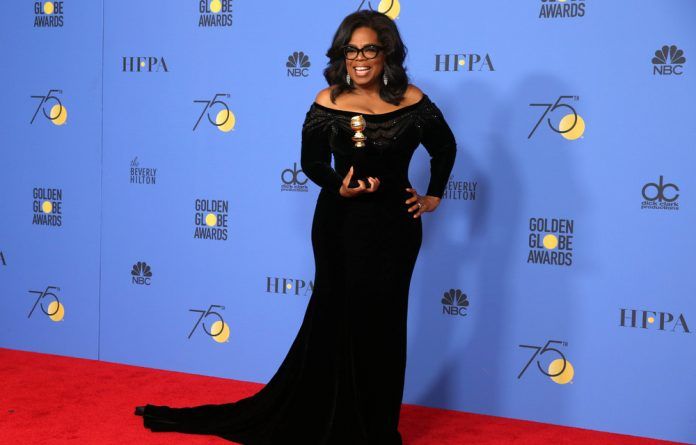 Oprah Winfrey poses backstage with her Cecil B. De Mille Award at the 75th Golden Globe Awards.