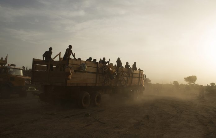 Trucks carrying internally-displaced Muslims arrive after having travelled in a convoy escorted by the African Union operation in CAR
