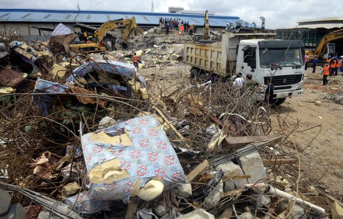 Rescue workers clear the debris of the collapsed guesthouse at TB Joshua's Synagogue Church of All Nations in Lagos.