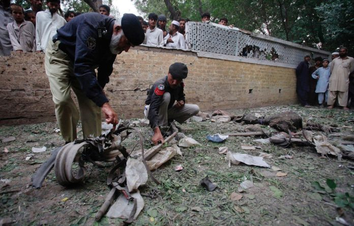 Policemen survey the site of a bomb attack outside a shrine in Peshawar on Thursday June 21