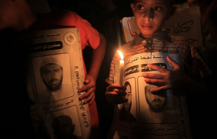 Palestinian children light candles during a rally held in Gaza City.