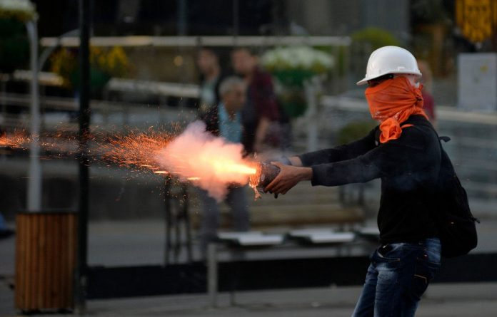 A protester fires firecrackers at riot polic  during a demonstration in Ankara blaming the ruling AK Party government for the Soma mining disaster.