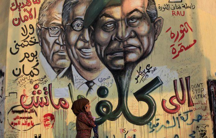 Graffiti showing faces of ousted Egyptian president Hosni Mubarak
