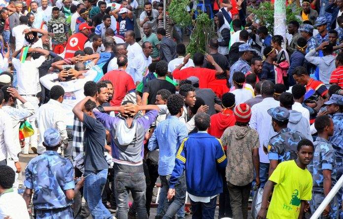 Ethiopians react after an explosion during a rally in support of the new Prime Minister Abiy Ahmed in Addis Ababa
