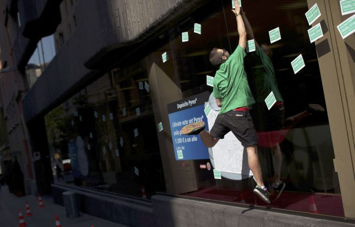 A demonstrator jumps as he fixes a sticker on the glass of a bank during a protest demanding the stop of planned foreclosures